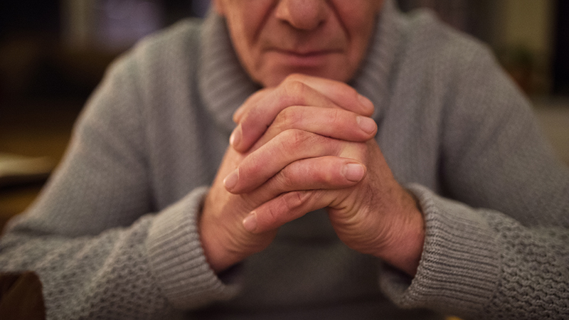 Старик сидит сложа руки вместе