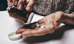 Старые руки держат таблетки